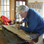 Woodcarving a house signboard during a woodcarving course