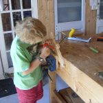 Young boy carving sign for bedroom