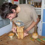 Polishing a finished carving of bulldog with wax polish