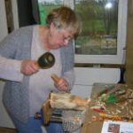 Retired lady woodcarver carving using yew wood