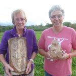 Two happy woodcarving students with their squirrel relief and a Yeti in walnut wood