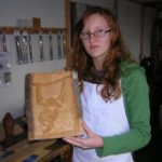 girl holding relief carving of gorilla made during woodcarving course in devon